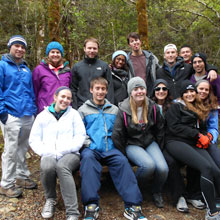 group of 10 students outdoors in woods